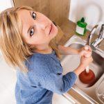 a woman unblocking a sink